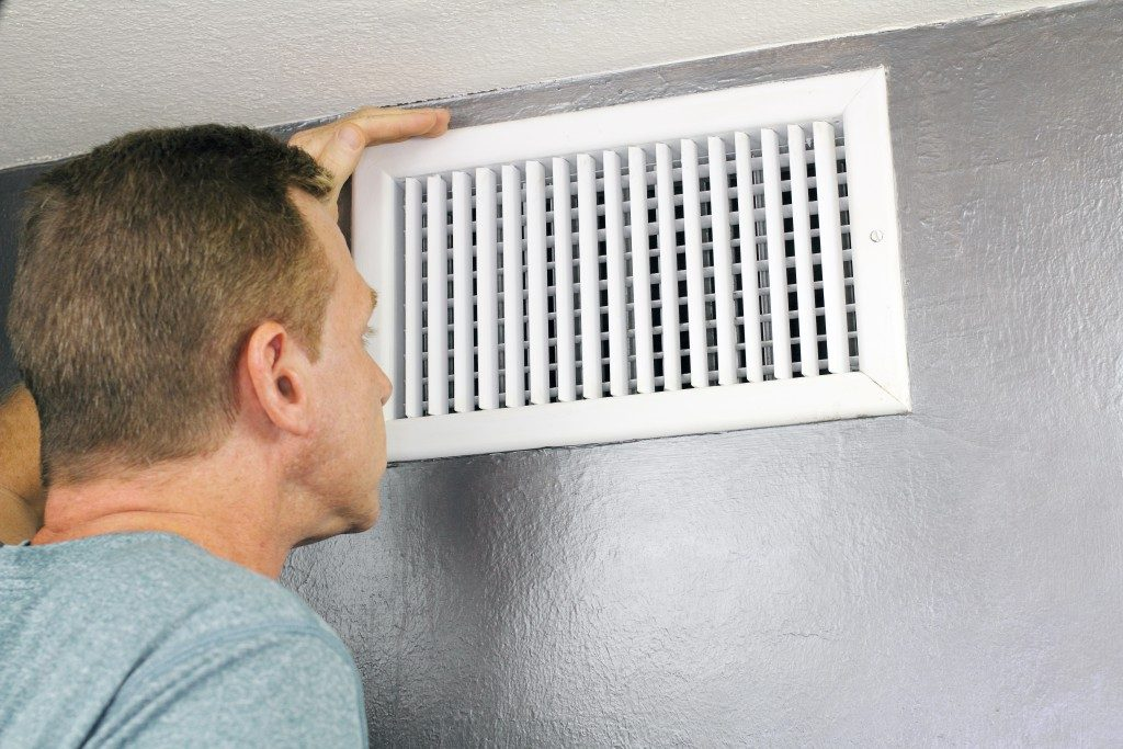 Man checking vent