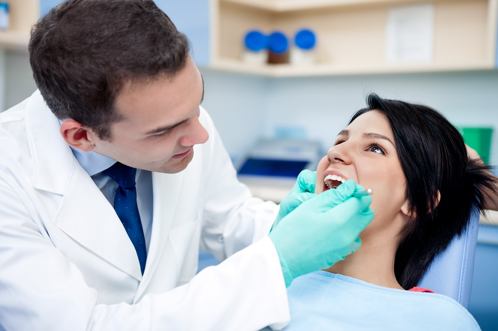 Dentist checking the teeth of the patient