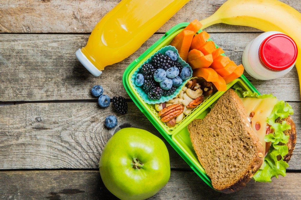 fruits, vegetables, and a sandwich in a lunchbox