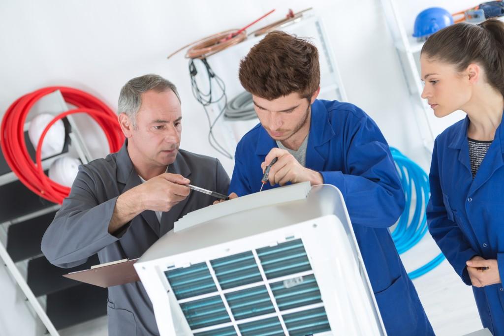 men repairing aircon