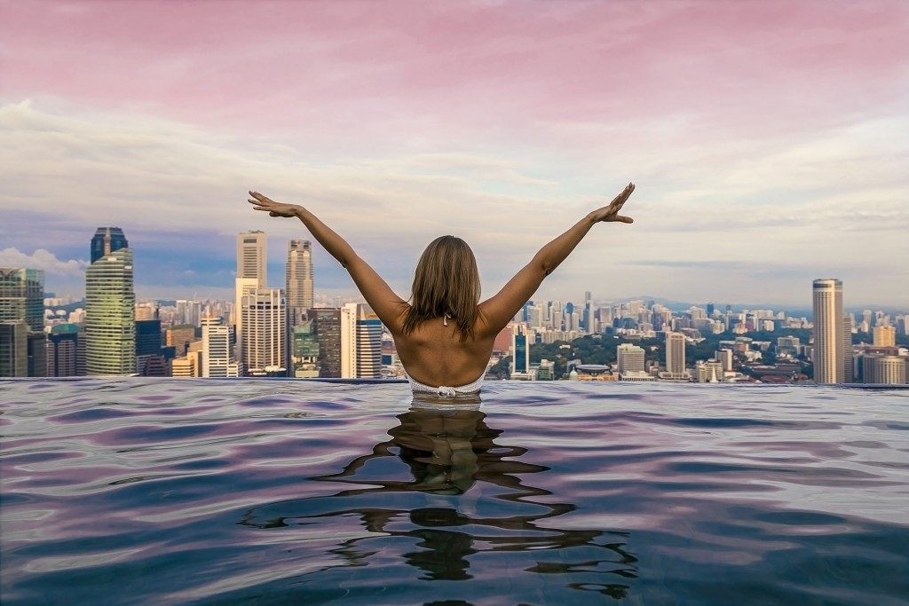 Girl with her back in the pool with overlooking view