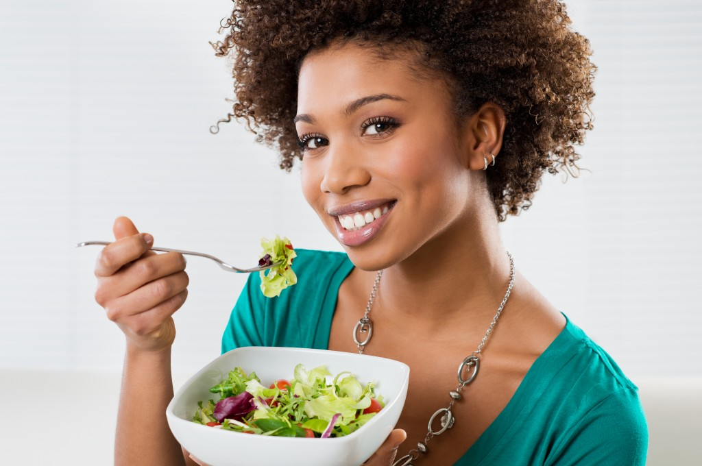 Woman eating salad in a bowl