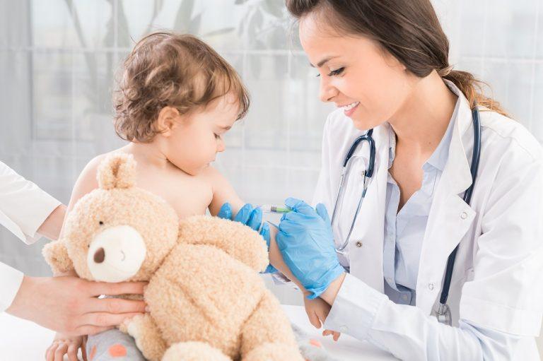pediatrician injecting vaccine to baby