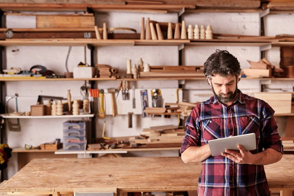 an artisan holding a tablet with woodworks at his back