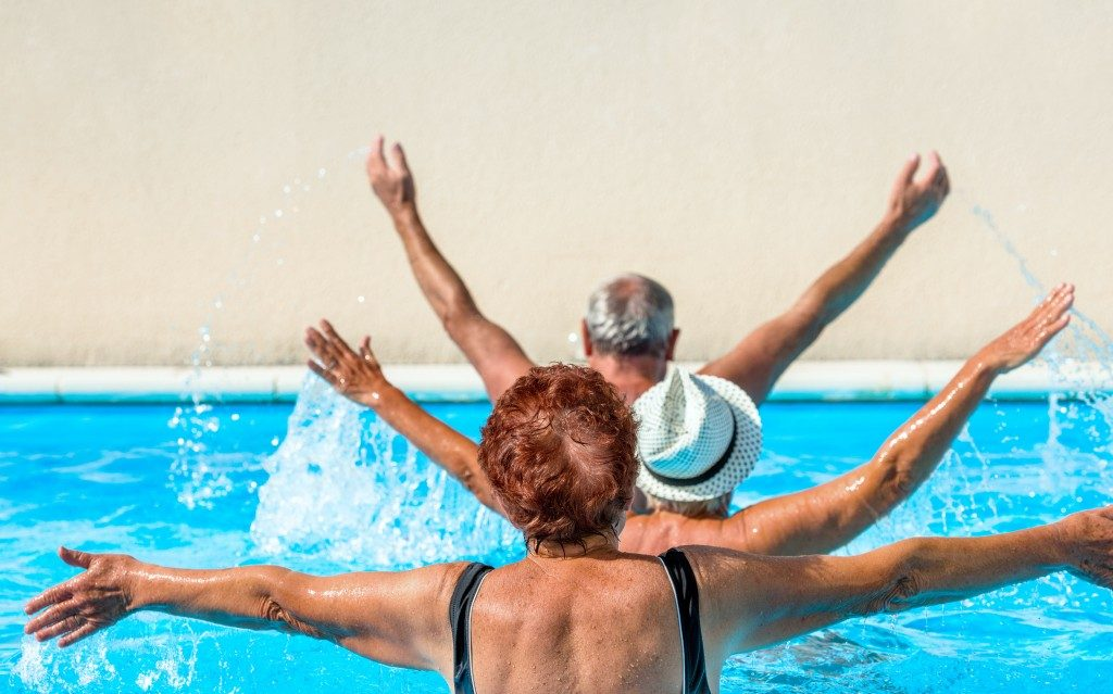 person aged group doing water aerobics in a swimming pool