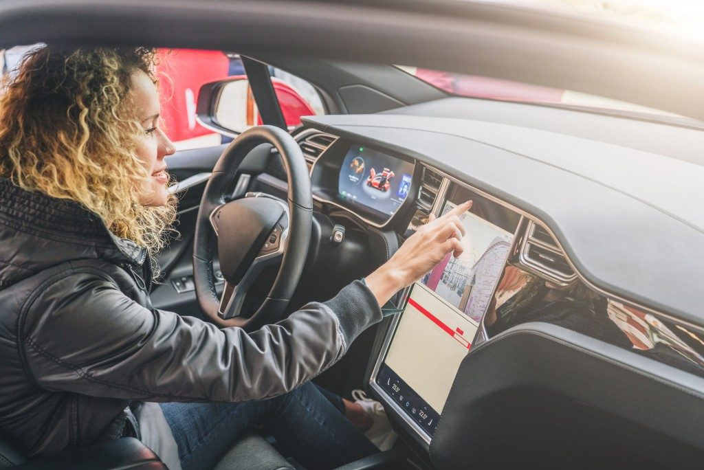 Young woman sits behind wheel in car and uses an electronic dashboard
