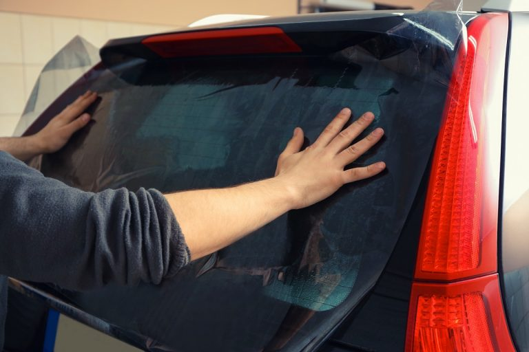 man wiping his car's tinted window