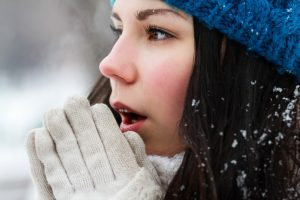 woman breathe with warm air on her frozen hands