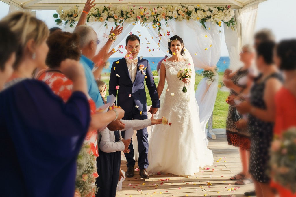 smiling newlyweds on the luxury outdoor wedding ceremony in haze tent near the ocean