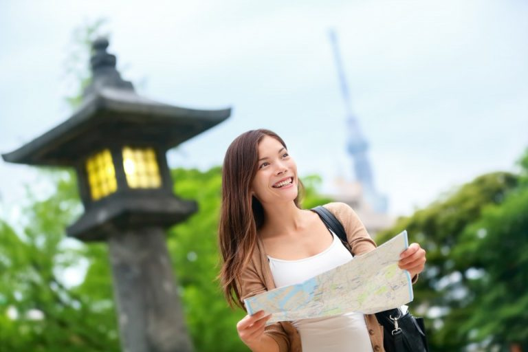 Asian tourist woman with map searching for directions with the Tokyo Skytree tower in the background