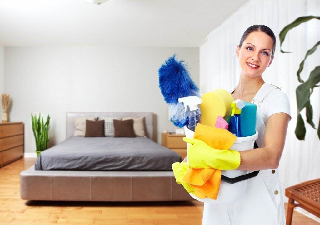 Woman holding cleaning materials inside the bedroom