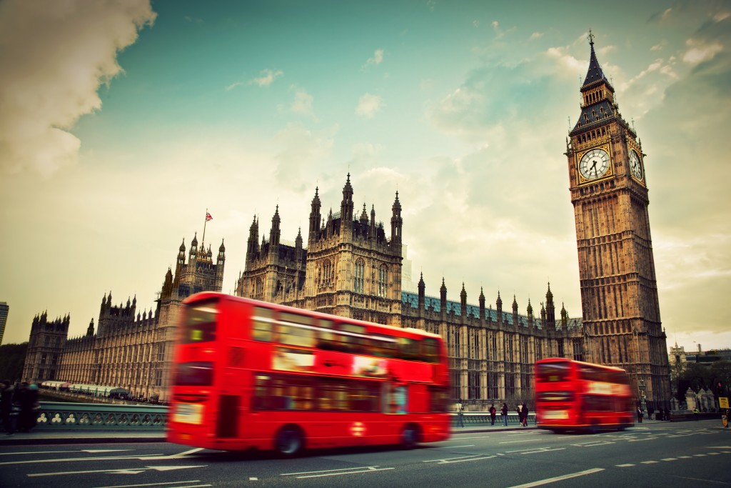 Red bus in motion and Big Ben, the Palace of Westminster