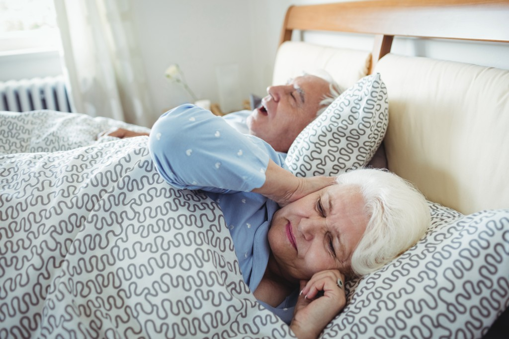 Man snoring and woman covering her ears while sleeping on bed in bedroom