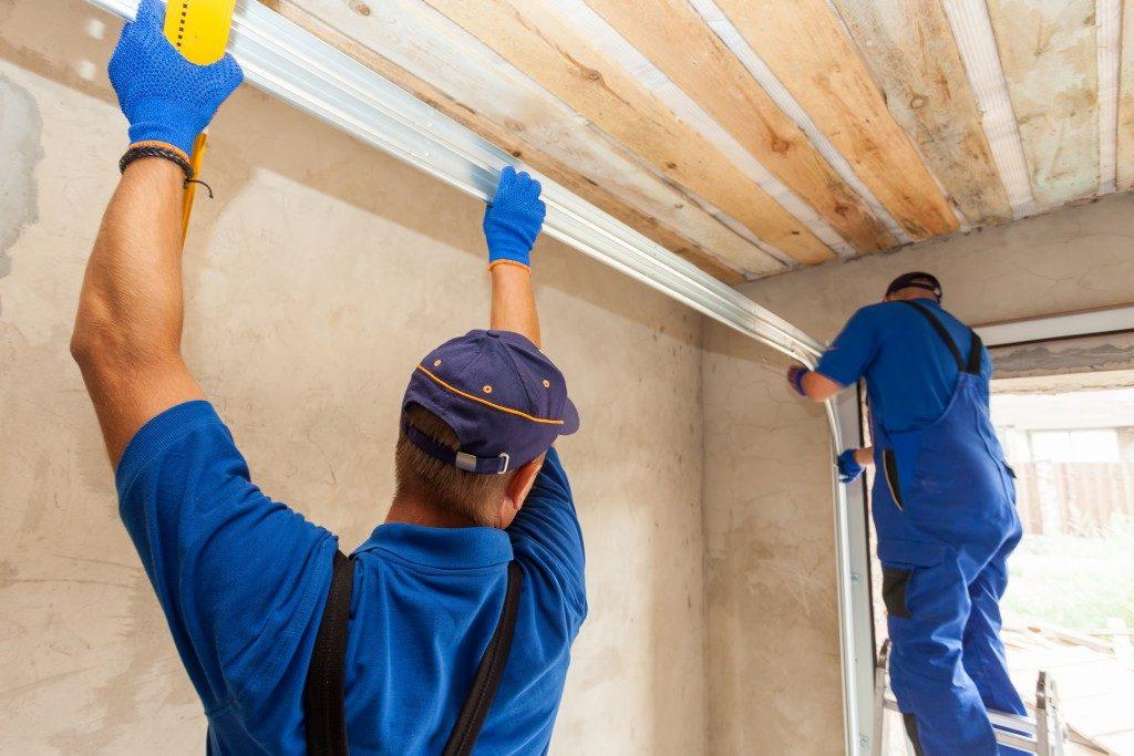 two contractors installing a garage door