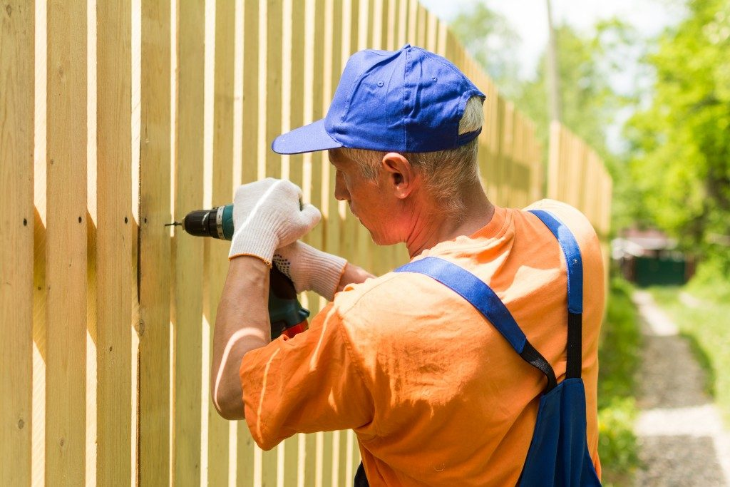 man repairing fence with a drill