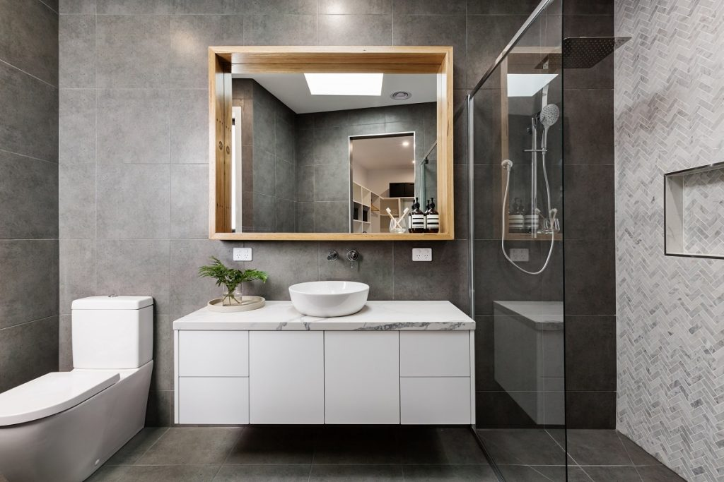 modern bathroom with gray tiles and big mirror