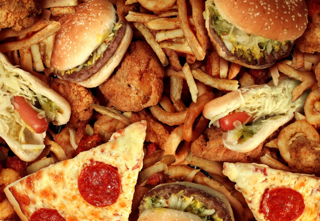 Fast food concept with greasy fried restaurant take out as onion rings burger and hot dogs with fried chicken french fries and pizza as a symbol of diet temptation resulting in unhealthy nutrition
