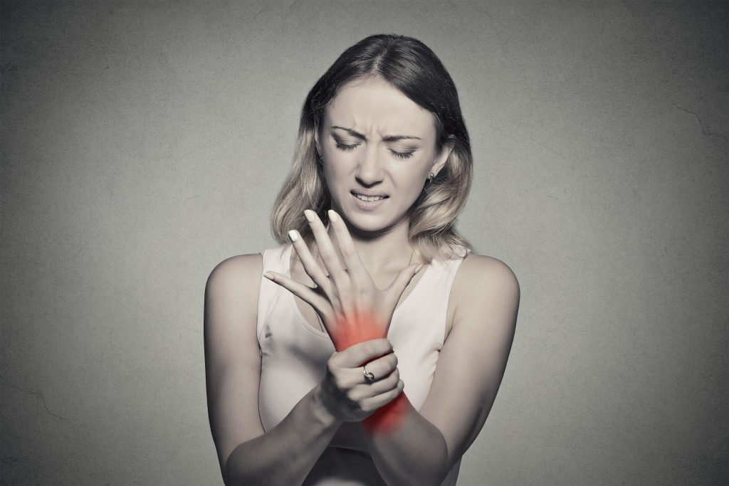 woman troubled, holding her left hand