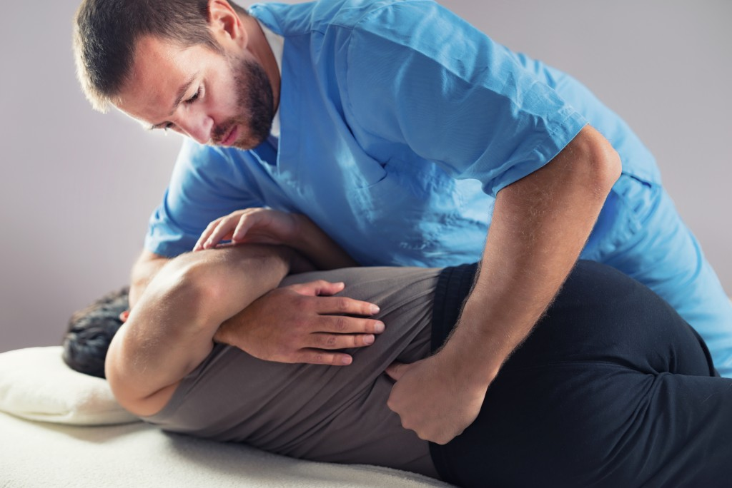 Chiropractor popping back of patient