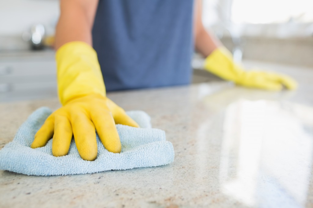 person cleaning the kitchen counter
