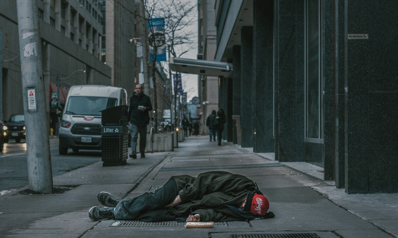 homeless person sleeping on the sidewalk