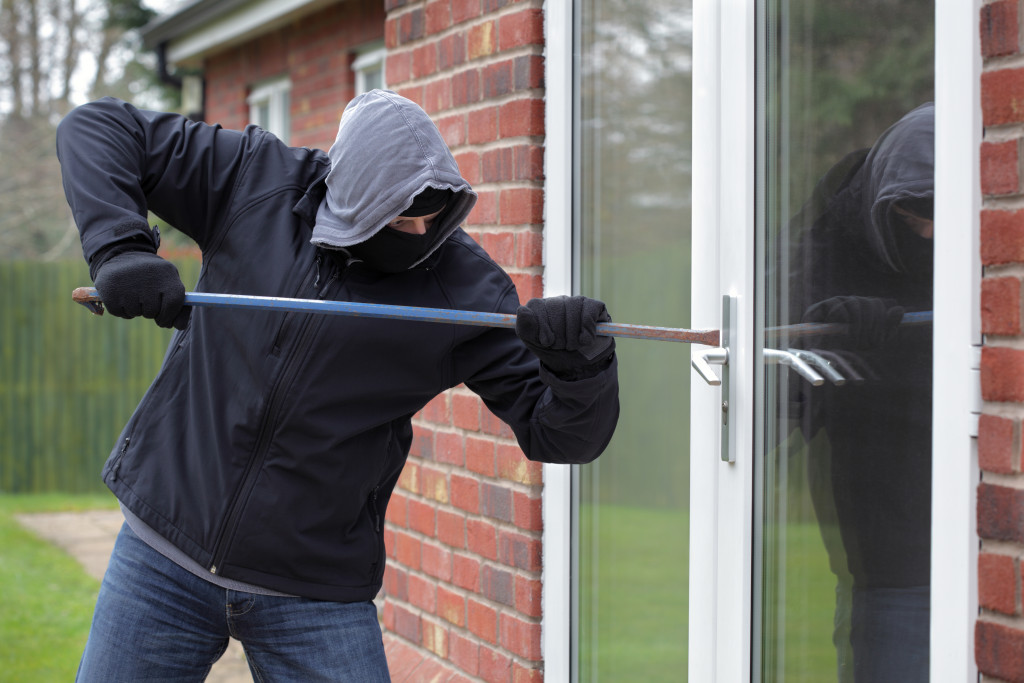 man breaking in with crowbar